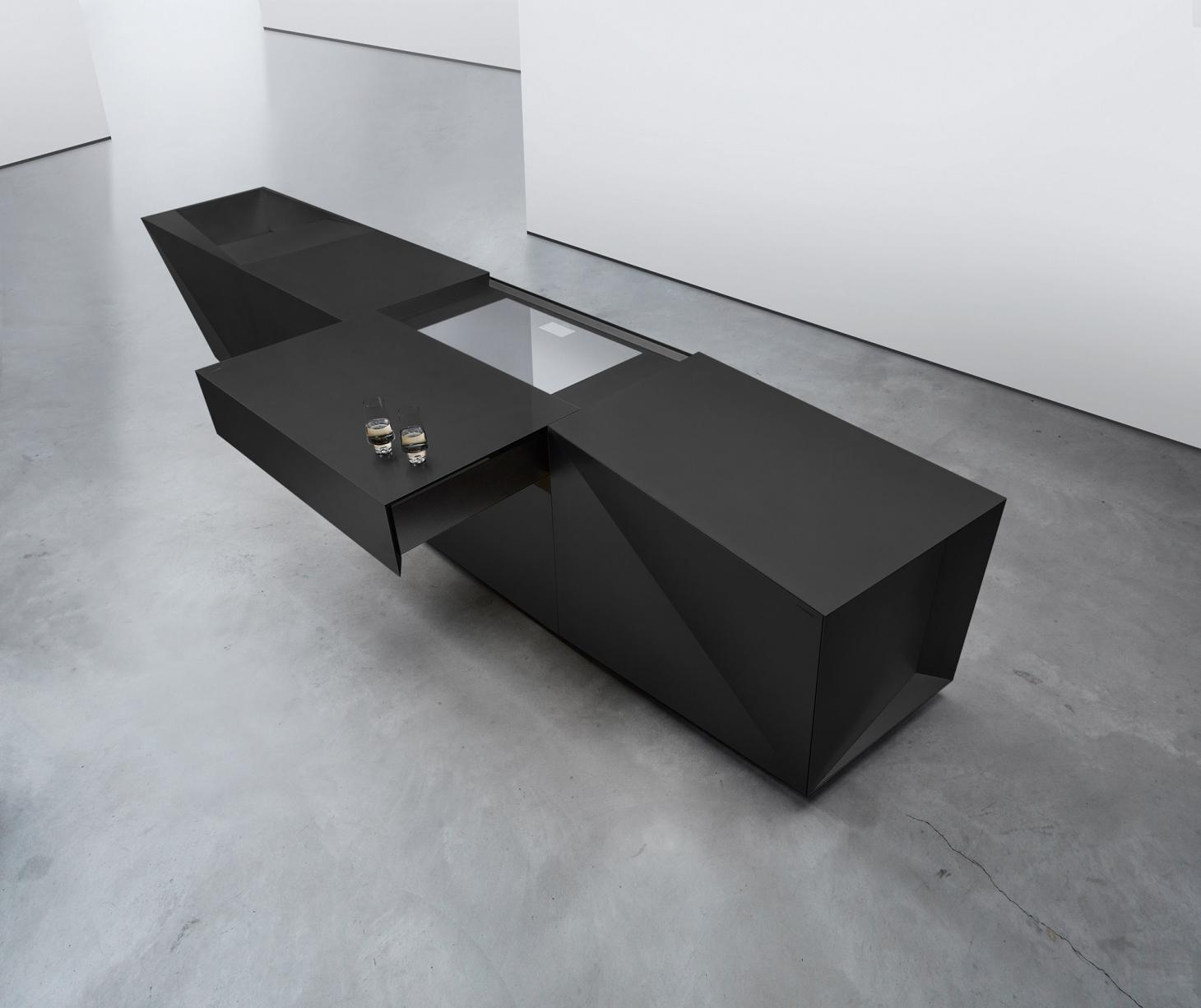 An aerial view of a Steininger kitchen island in black on a concrete floor