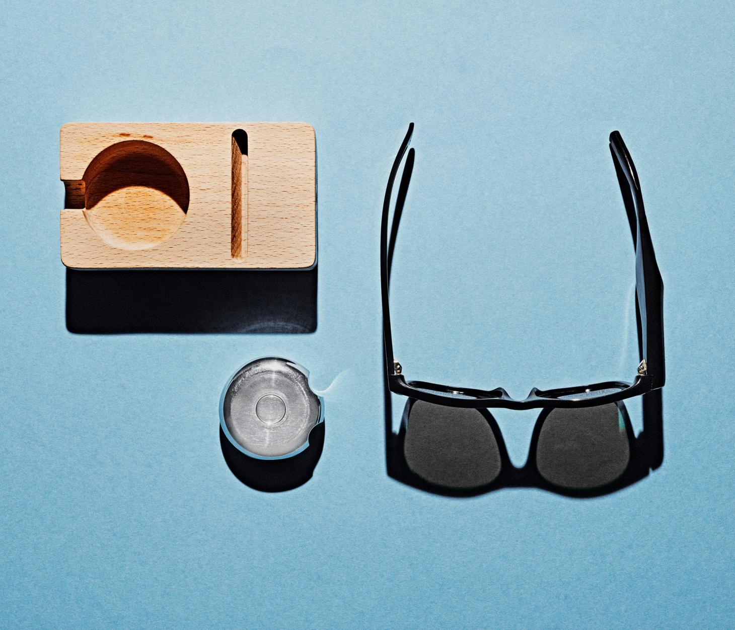 wooden holder, a vibrating silver bean-shaped nugget and a pair of sunglasses