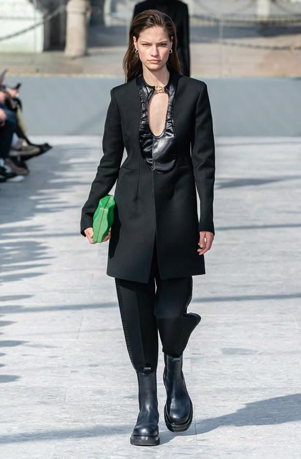 Woman wears black cut out tuxedo with stomper boots and a green bag