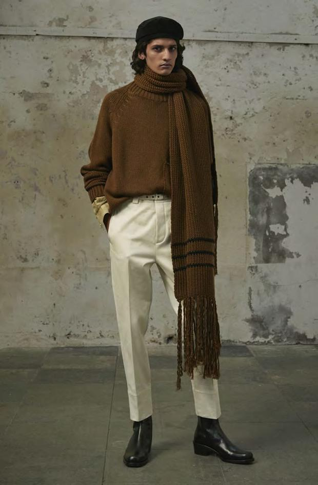 Man wears brown scarf with white trousers
