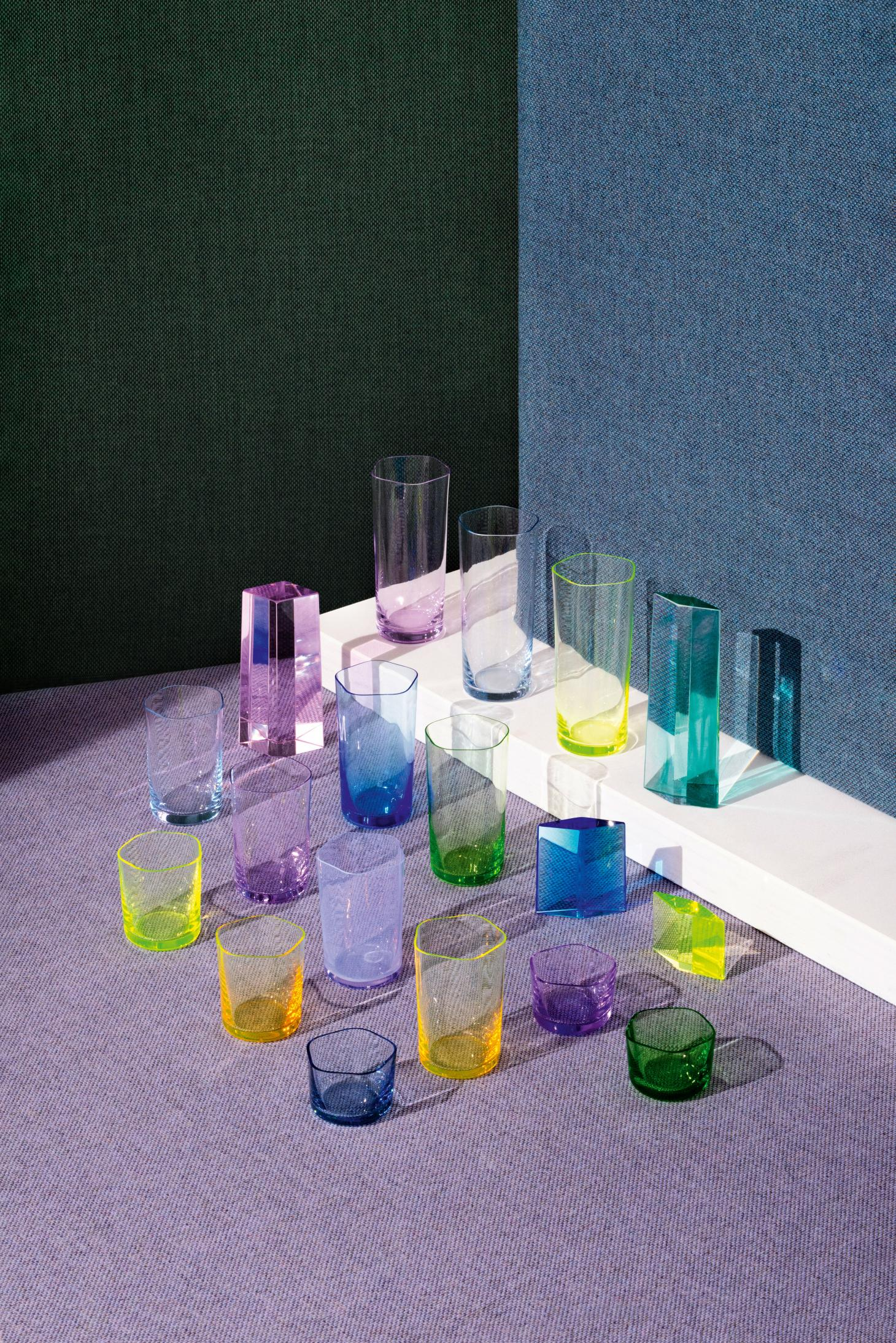 Several thin glasses of different sizes, colours include yellow, lilac, green, blue and pink