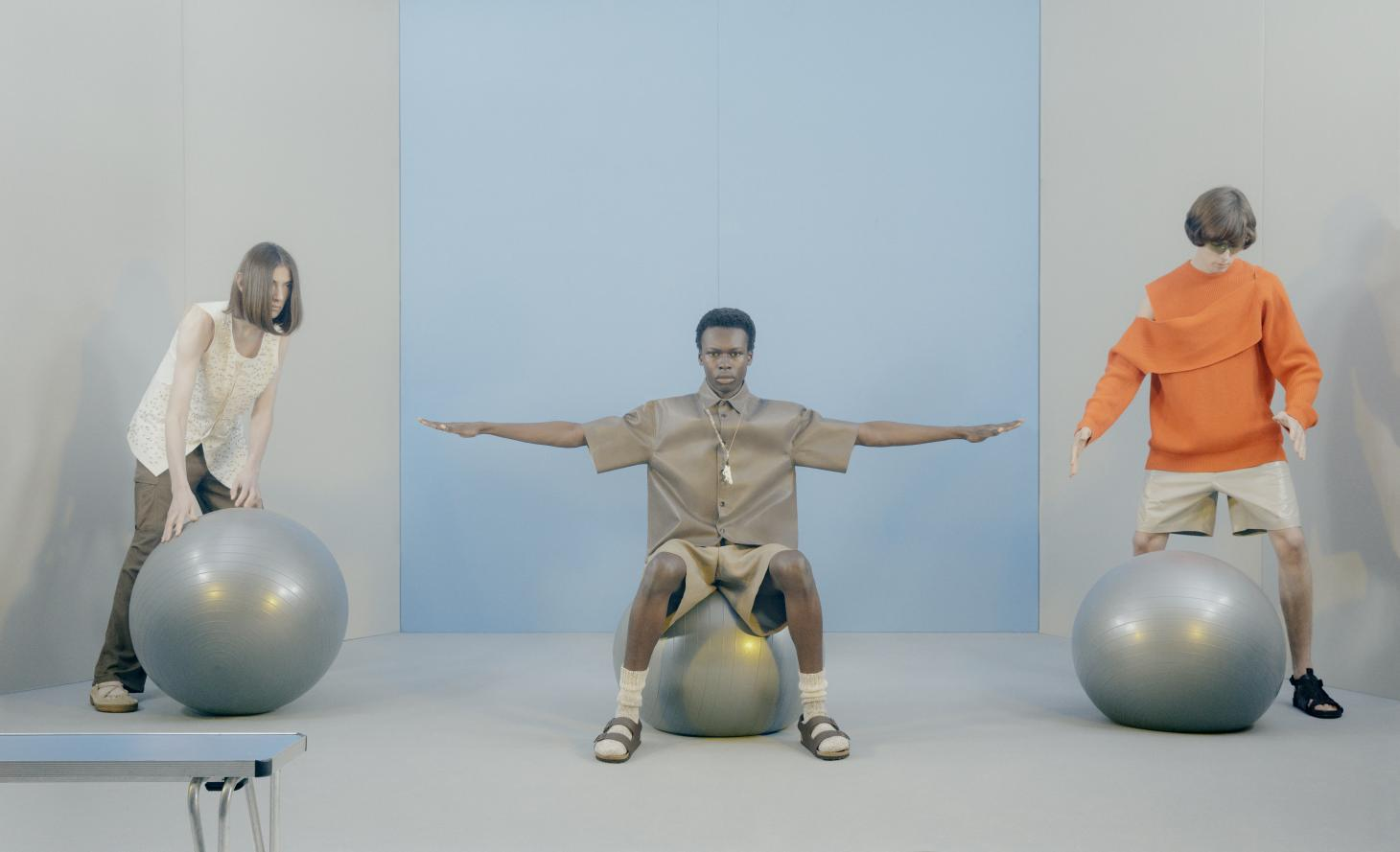 three men balancing on silver balls