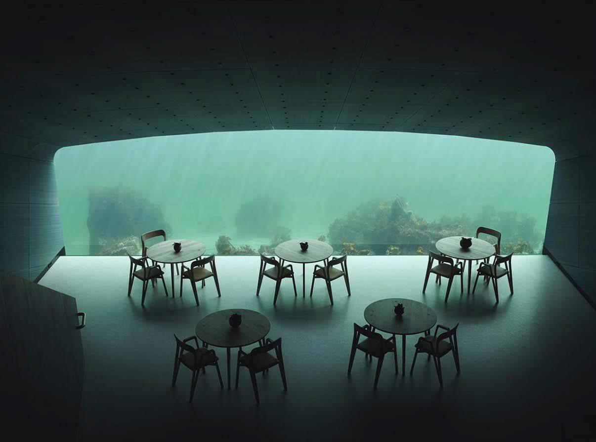 An interior of an underwater restaurant, the table and chairs face a glass wall looking out into the seabed