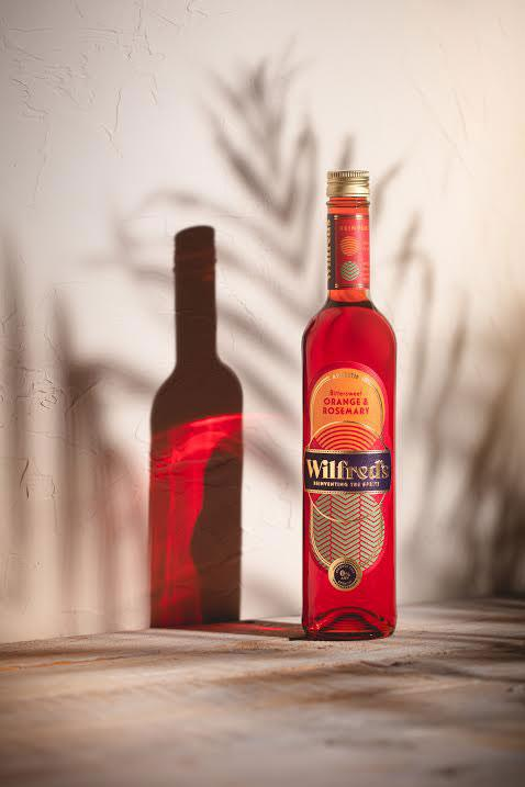 wilfred's non-alcoholic orange and rosemary aperitif in glass bottle against beige background