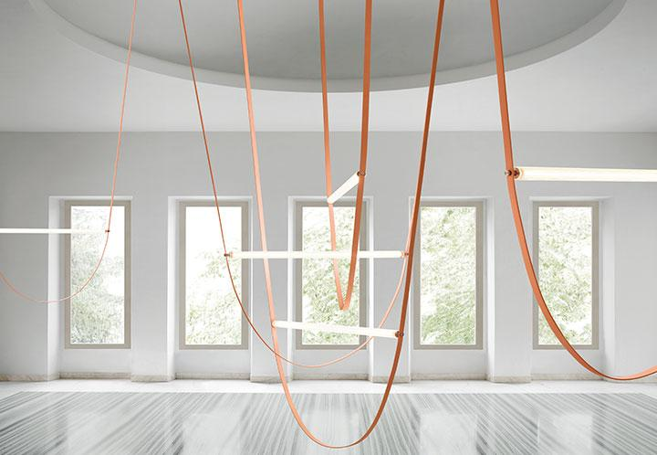 A large bright room with five tall windows and striped marble floor. An installation of Formafantasma's Wireline lights for Flos features several pink downward arches with tube light source