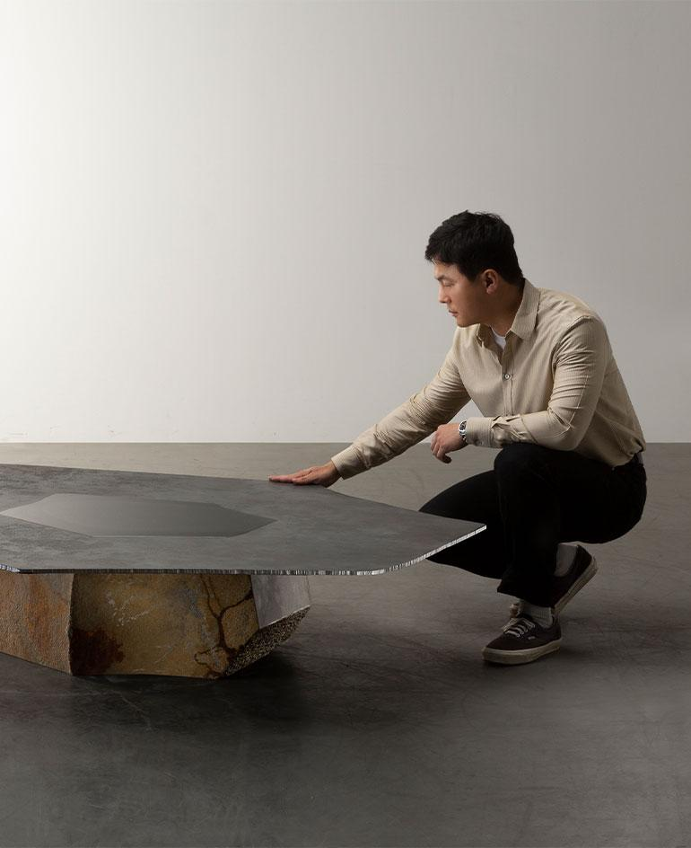 Portrait of Wonmin Park with a low table from the collection, made of raw stone and steel top