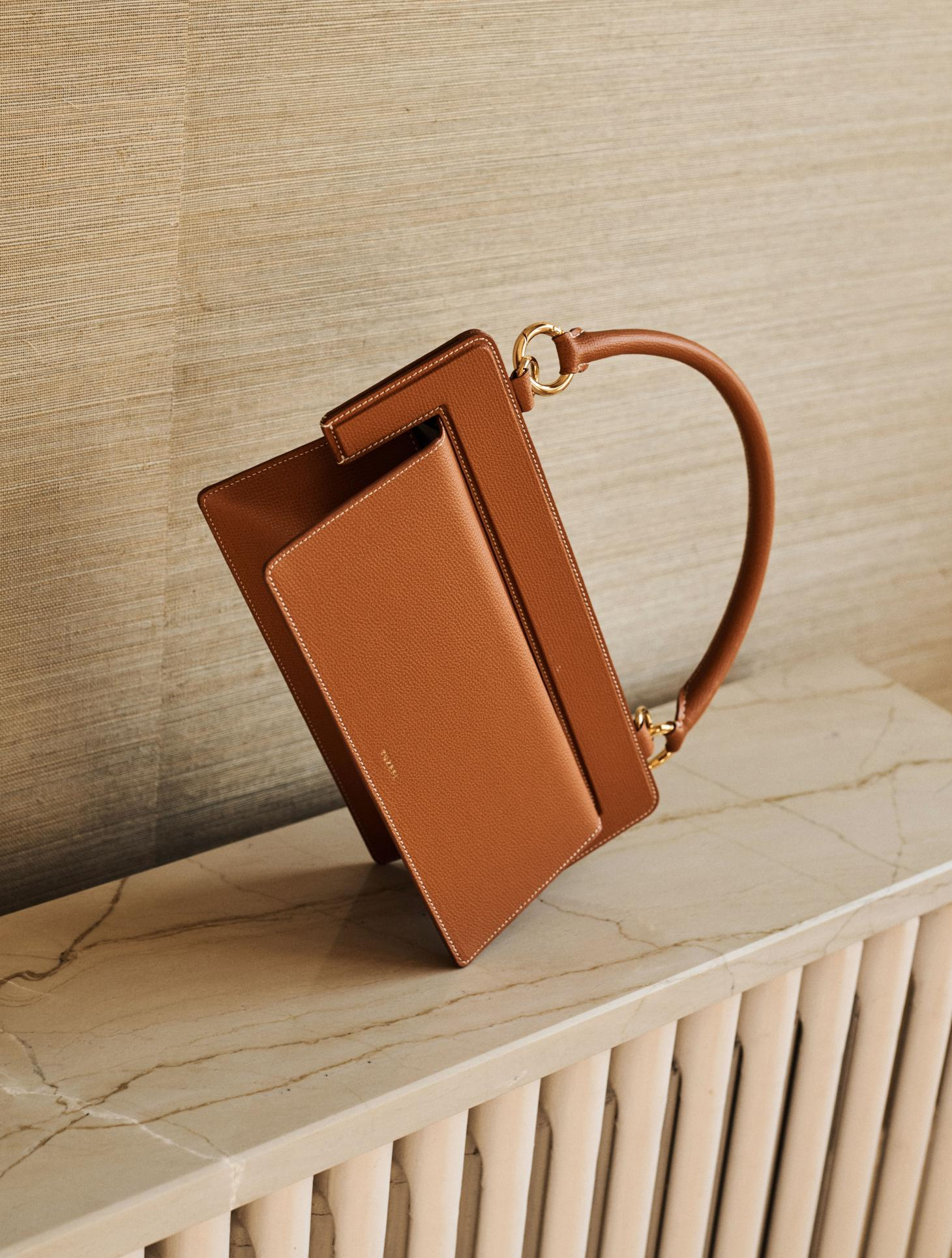 Tan leather bag stands on its side