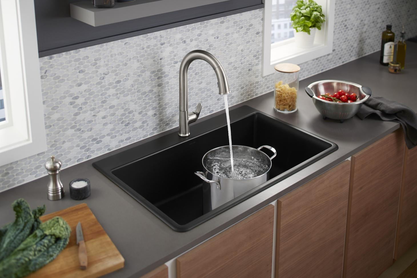 A kitchen tap with water coming out into a pot inside the sink